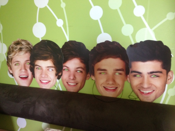 Scary One Direction masks that line Sakina's bed